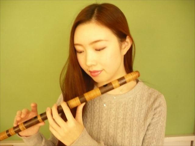 篠笛の指孔の位置を確認する女性